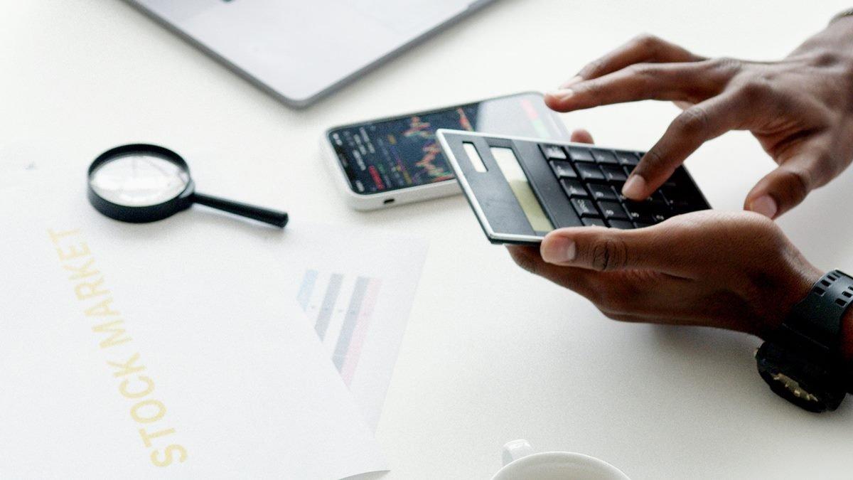 Seseorang yang sedang menggunakan kalkulator untuk menghitung harga book building saham IPO.