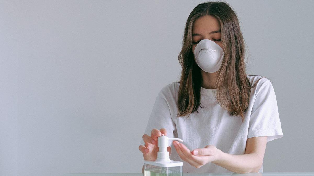Seorang wanita yang sedang menggunakan hand sanitizer.