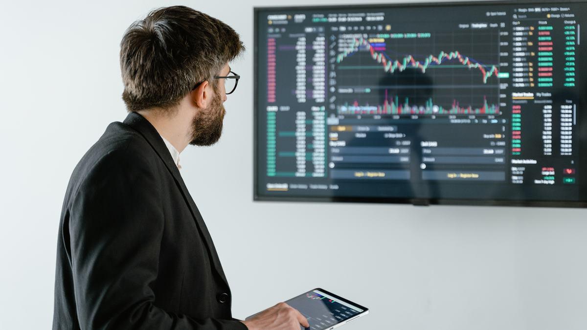 Seorang pria yang sedang melihat pergerakan saham.