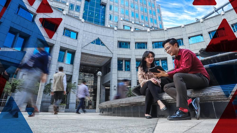 Dua orang yang sedang berbincang di depan gedung Bank Indonesia.