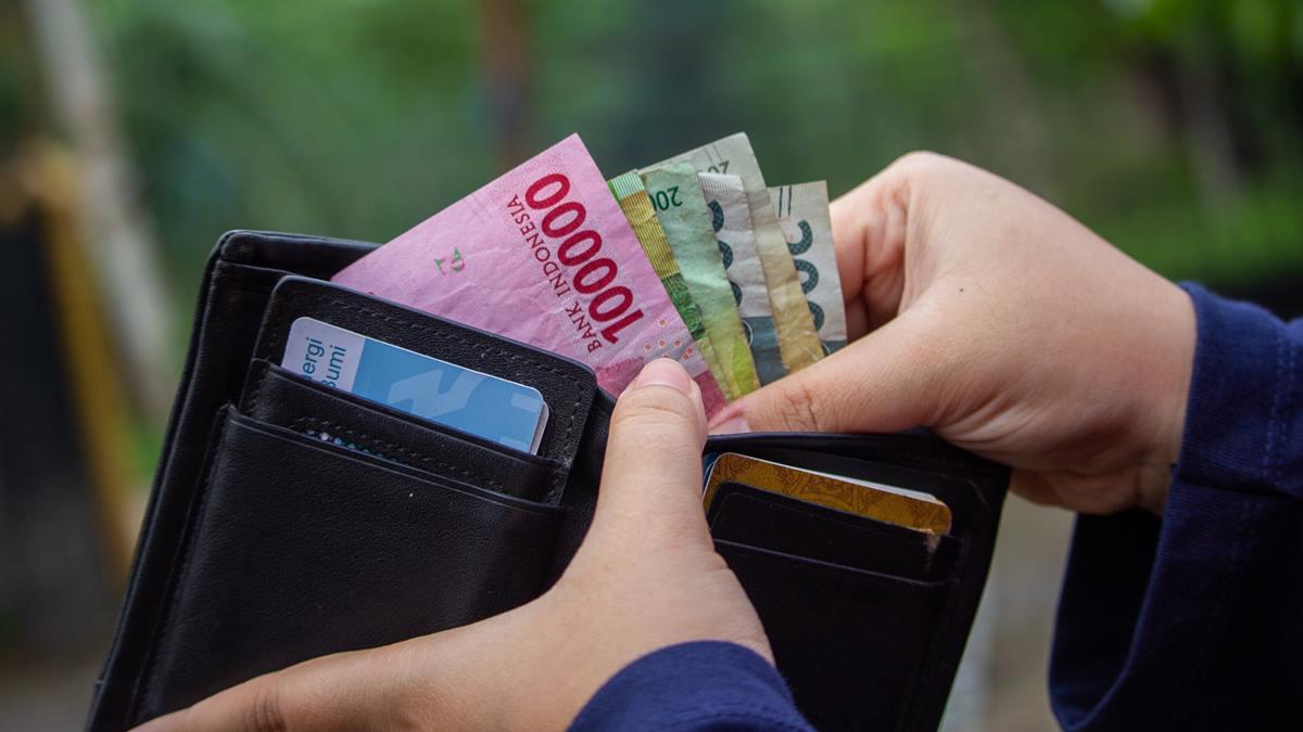 Seseorang mengambil uang dari dompet.