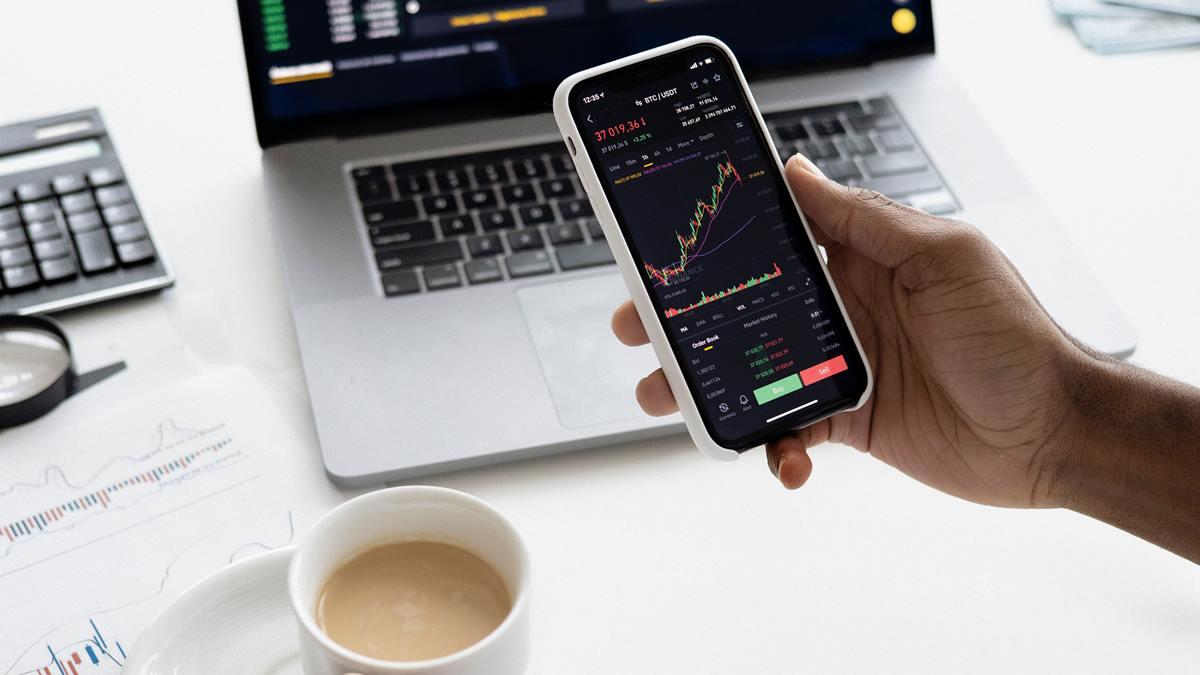 Seseorang sedang memegang ponsel dengan layar yang menunjukkan grafik saham.