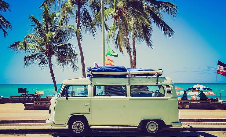 Mobil VW Combi yang terparkir di pinggir pantai sangat cocok menggambarkan liburan impian di musim panas