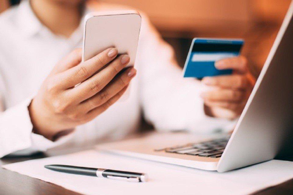 seorang pria menggunakan ponselnya untuk belanja online
