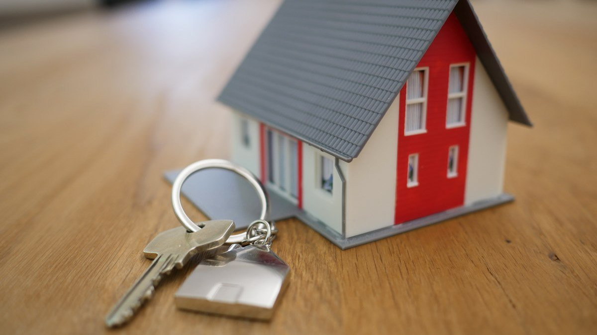 Miniatur bangunan rumah dan sebuah kunci rumah.