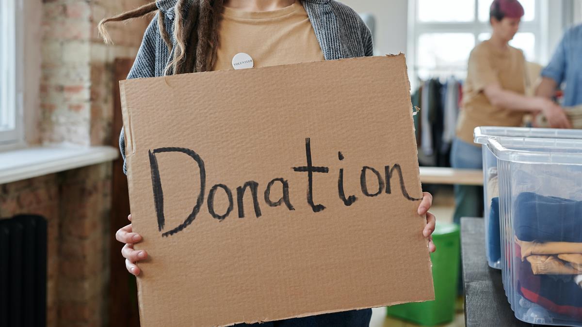 Seorang wanita yang sedang memegang kardus bertuliskan 'donation'.